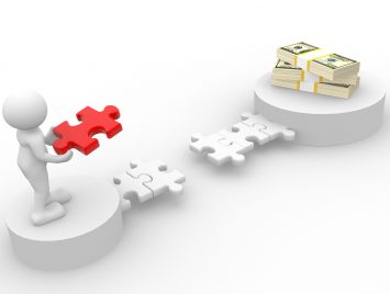 man holding puzzle piece to finish bridge towards a stack of money